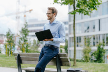 Young Businessman Sitting On Park Bench, Using Laptop