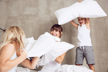 Mother And Children Having Fun, Having A Pillow Fight In Bed