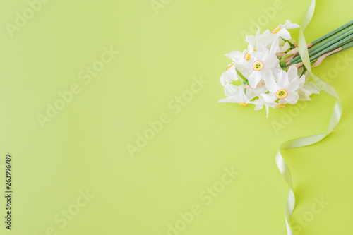 La pose en embrasure Narcisse Flat lay composition with white daffodils on a green background