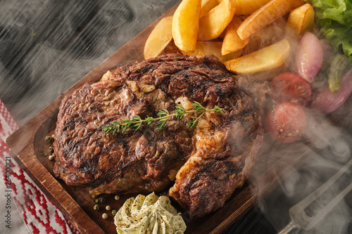 Fotografia Ribeye steak with potatoes, onions and baked cherry tomatoes
