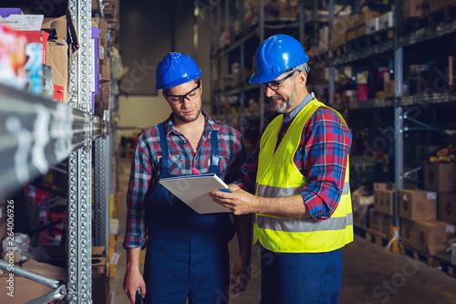 Obraz na płótnie Two warehouse workers filling in document