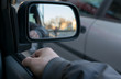 a man's hand on the car door on the background of a female silhouette in the mirror of the rear view mirror