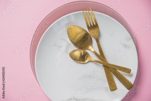 Marble Plate Gold Knifefork And Spoon On Pink Backgrounddishes