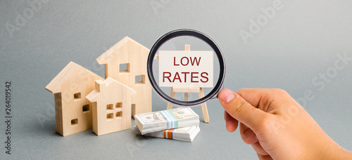 Fototapeta A magnifying glass is looking at a poster with the word Low rates and wooden house. The concept of reducing interest rates on mortgages. Housing on credit. Rents. Real estate capitalization. Insurance obraz