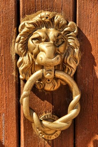 Fotografía  Vintage door knocker lion shaped on brown wooden door