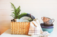 Stack Of Modern Tableware In Basket. Cleaning And Organizing Kitchen In Spring