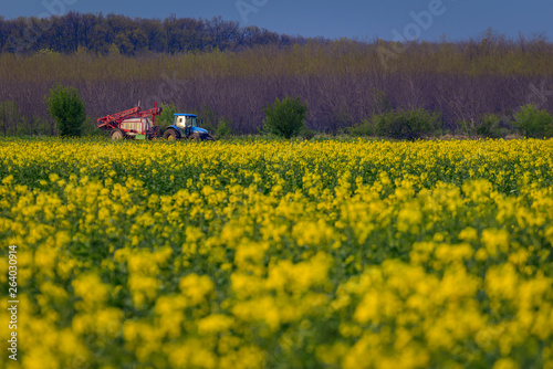 Blue tractor machinery used in agriculture spraying insecticide from a tow on a Canvas Print