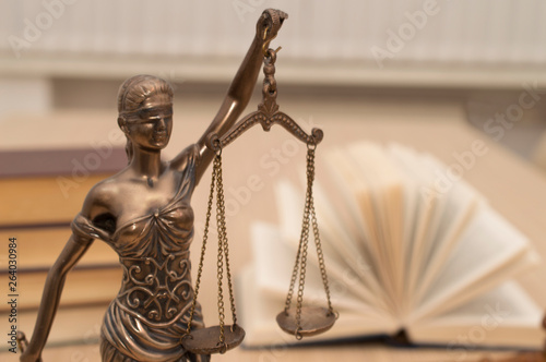 Fototapety, obrazy: statue of justice on wooden table against the background of an open book.