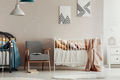 Aluminium Prints Equestrian Fashionable retro armchair between two wooden cribs in cute twins nursery