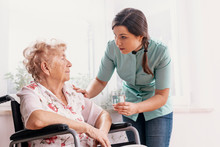 Senior Grandmother On Wheelchair, Supporting Nurse Giving Her Glass Of Water