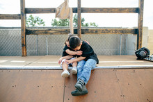 Brother And Sister Hug While Sitting On Half Pipe