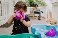 Girl Playing With Water Toys While Dad Works In Background
