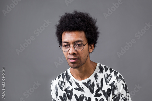 Curly African man with glasses on grey background Canvas Print