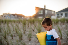 Boy Walking To Beach At Sunset While Carrying Yellow Bucket
