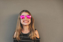 Young Girl Standing Against A Wall Smiling With Pink Sunglasses