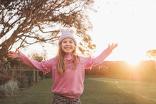 Smiling Young Girl Throwing Leaves In The Park At Sunset