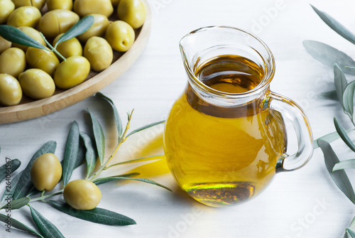 Glass bottle of olive oil and olive tree branch, raw turkish green