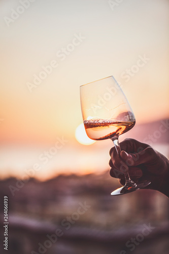 Photo  Glass of rose wine in man'€™s hand with sea view and sunset at background, close-up