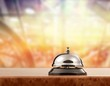Vintage hotel reception service desk bell on blurred background, bokeh