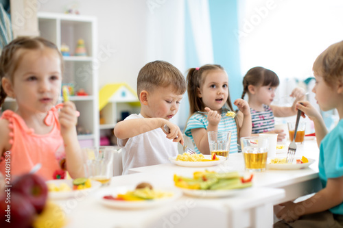 Fotografering Group of preschool kids have a lunch in daycare