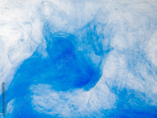 Stickers pour porte Eau Droplet of blue paint mixing with water, close up view. Blurred background. Acrylic clouds in liquid, abstract background. Blue abstract pattern of acrylic paint in water. Ink in liquid