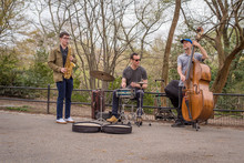 A Jazz Trio Featuring Alto Saxophone, Standup Bass, And Drums Plays In New York City's Central Park Amongst The Trees On A Cloudy Day