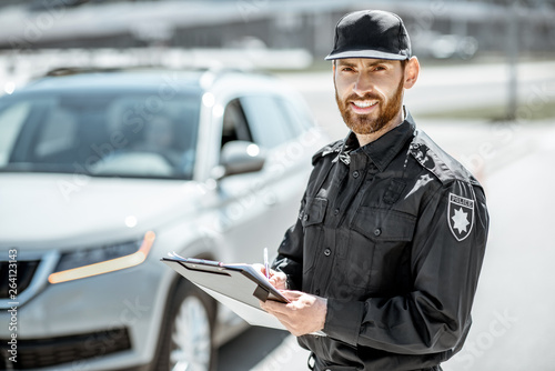 Portrait of a handsome policeman in uniform standing in front of a car on the ro Fototapet