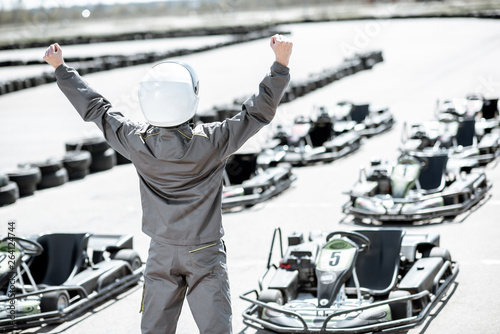 Obraz na plátně Portrait of a happy racer in protective sportswear standing as a winner of a go-