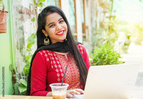 Fototapeta Indian woman with laptop in a cafe
