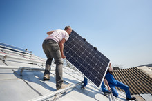 Male Workers Installing Stand-alone Solar Photovoltaic Panel System. Electricians Lifting Blue Solar Module On Roof Of Modern House. Alternative Energy Sustainable Resources Renewable Concept.