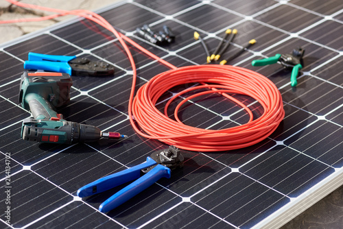 Leinwanddruck Bild - anatoliy_gleb : Close-up view of different details and instruments for mounting and connecting solar photovoltaic system. Objects laying on blue solar panel. Alternative energy resources renewable ecology concept.