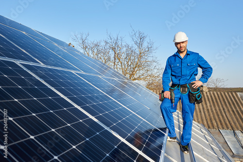 Smiling engineer in blue suit and protective helmet installing solar photovoltaic panel system using screwdriver. Electrician standing on roof of modern house. Alternative energy ecological concept.