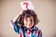 Leinwandbild Motiv Kid boy with question mark. Children, education and emotions concept
