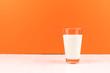 Leinwanddruck Bild - orange background with glass milk