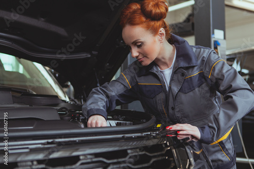 Experienced female mechanic servicing an automobile at her workshop. Lovely repairwoman working at the garage. Beautiful female technician in grey uniform working under the hood of modern SUV car, cop - 264167795