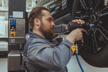 Handsome Bearded Car Mechanic Servicing An Automobile At His Workshop, Torquing The Lug Nuts. Attractive Male Technician In Grey Uniform Repairing Wheels Of A SUV Vehicle. Safety, Insurance Concept