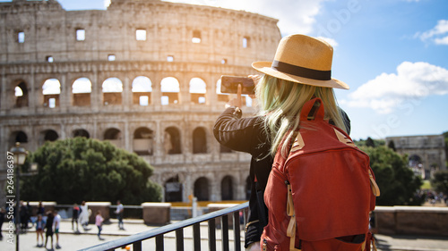 Photo  Back view of young woman with hat she's take a picture by smartphone at Colosseum in Rome, Italy
