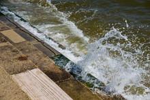 Ocean Sea Tide Breaking Over Stone Seaweed Covered Steps