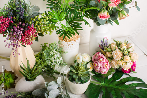 Various artificial flowers, bouquets in vases, succulents