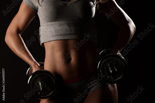 obraz lub plakat Young fit girl working out with weights - Portrait of pretty young woman lifting dumbbells during exercising