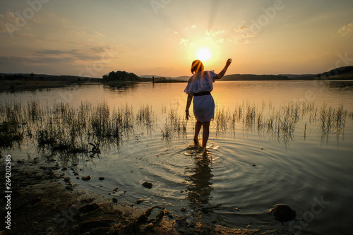 Fototapeta  a woman in dress with her feet in the water of a lake in front of a sunset, Occi