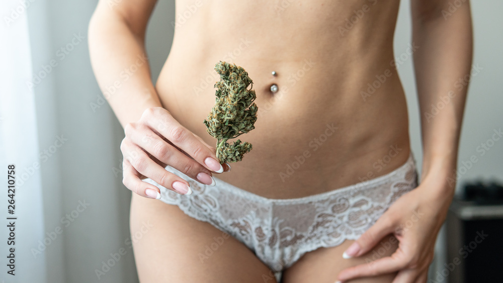 Fototapety, obrazy: a young girl holds a marijuana cone in front of her. Women's health while smoking marijuana.