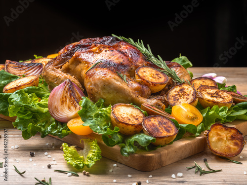 Roasted chicken with grilled potatoes and onion, yellow tomatoes, fresh green salad on wooden table. Owen cooked meat with vegetables. Original food serving in restaurant, cafe. Holiday dinner.