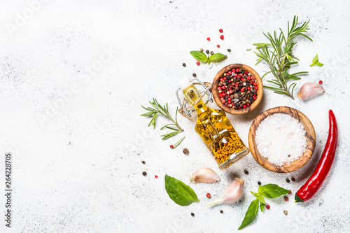 Photo  Spices, herbs and olive oil over white stone table.