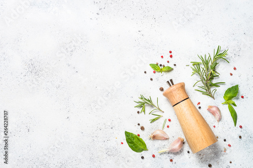 Fotomural  Pepper mill with fresh herbs on white.