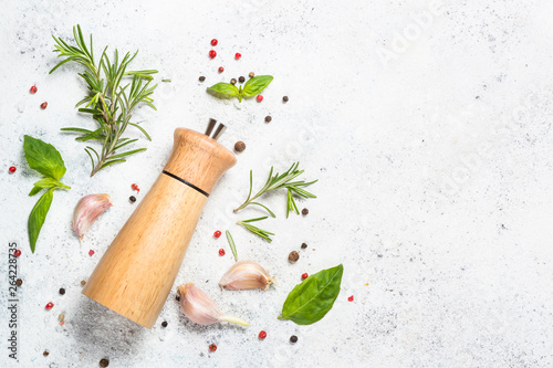 Fotografía Pepper mill with fresh herbs on white.