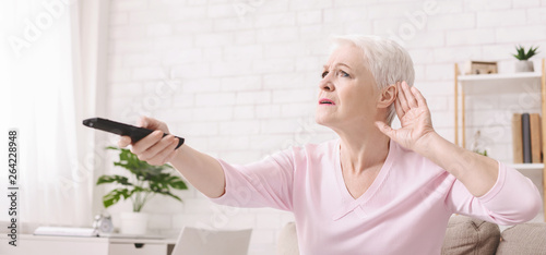 Foto  Elderly woman rising tv set volume with remote control