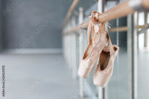 Pointe shoes hang on ballet barre in dance class room. Blurred background of ballet classic school.