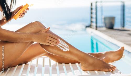 Woman putting tanning cream on legs Fototapeta