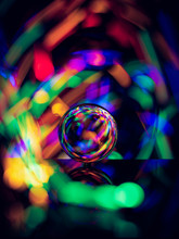 Crystal Ball On Reflective Surface With Colorful Lights Background